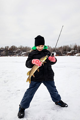A young boy catching a Northern Pike while ice fishing on Lake Wabamum during a winter family outing; Wabamun, Alberta, Canada - p442m2058090 by LJM Photo
