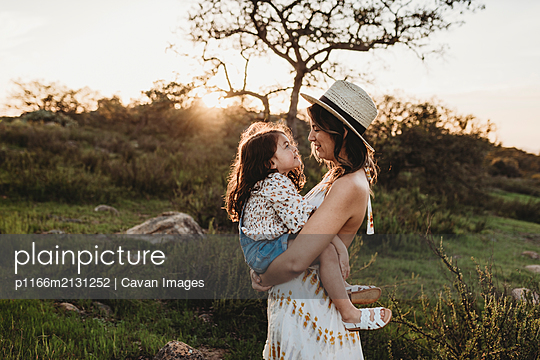 Side view of mother holding daughter while looking at each other - p1166m2131252 by Cavan Images