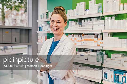 Happy pharmacist with arms crossed standing in chemist shop - p300m2243106 by Mareen Fischinger