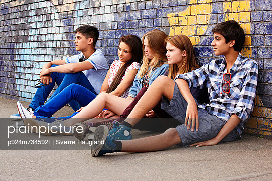 Teenagers sitting against a wall - p924m734592f by Sverre Haugland
