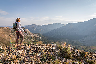 Young woman takes in the view, enjoying a rest on a morning trail run - p1166m2130617 by Cavan Images