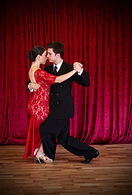 Tango dancers against red curtain - p1445m2128302 by Eugenia Kyriakopoulou