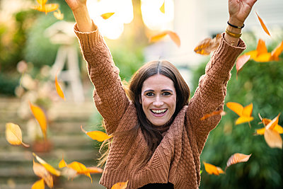 Cheerful woman throwing leaves during autumn - p300m2253214 by Annika List