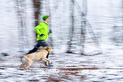 Young male athlete running in speed with dog during winter in forest - p300m2256630 by Stefan Schurr
