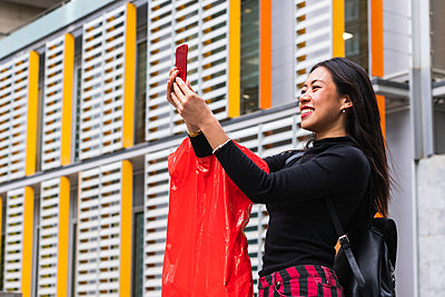 Woman smiling while taking selfie through mobile phone - p300m2276332 by NOVELLIMAGE