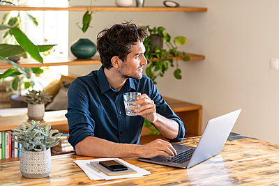 Thoughtful male freelancer having water while sitting with laptop at table - p300m2277464 by Steve Brookland