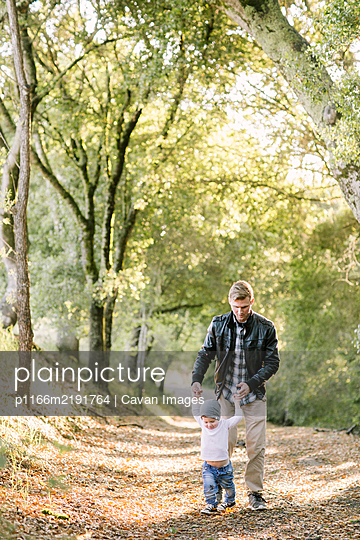 Toddler boy and young father walking on a hiking trail holding hands - p1166m2191764 by Cavan Images