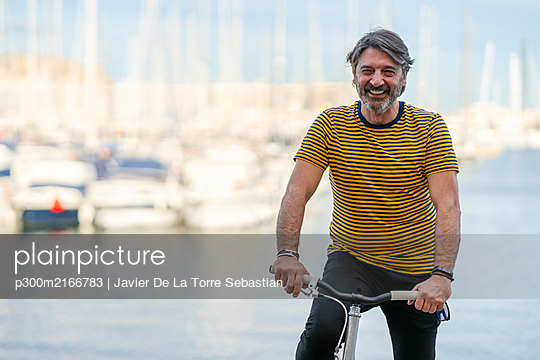 Portrait of laughing mature man  with bicycle in front of harbour, Alicante, Spain - p300m2166783 by Javier De La Torre Sebastian