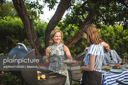 Smiling mother looking at daughter assisting in preparing food at barbecue grill in backyard during weekend party - p426m2135553 by Maskot
