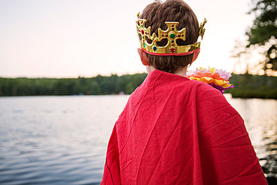 Rear view of boy wearing king costume by river against clear sky - p1166m1150466 by Cavan Images