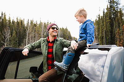 Happy father and son outside SUV at remote roadside - p1192m2094092 by Hero Images