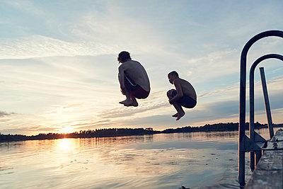 Boys jumping into lake - p312m1522073 by Johan Alp