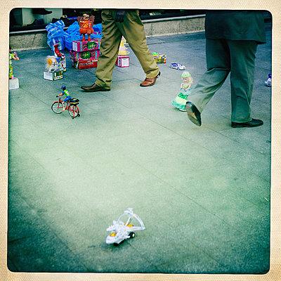 Nostalgisches Spielzeug und Fußgänger auf dem Gehweg - p819m972601 von Kniel Mess