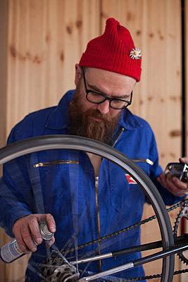 Mann repariert ein Fahrrad  - p906m1362796 von Wassily Zittel