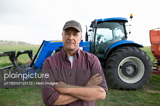 Portrait confident male farmer standing in front of tractor - p1192m2123172 by Hero Images