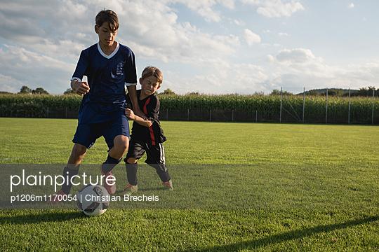 Zwei Jungen spielen Fußball - p1206m1170054 von Christian Brecheis