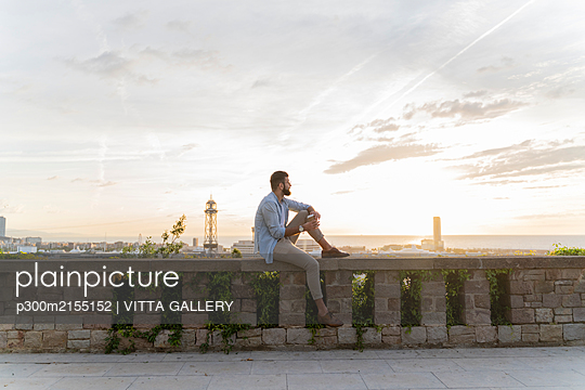 Man sitting on a wall on lookout above the city with view to the port, Barcelona, Spain - p300m2155152 by VITTA GALLERY