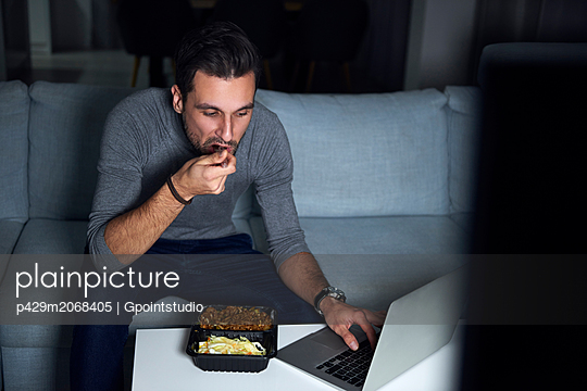 Young man sitting on sofa in evening eating takeaway and using laptop - p429m2068405 by Gpointstudio