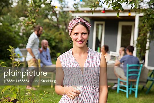 Junge Frau trinkt Weißwein im Garten - p788m1165364 von Lisa Krechting