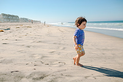 Side view of cute boy at beach against clear blue sky during sunny day - p1166m1210425 by Cavan Images