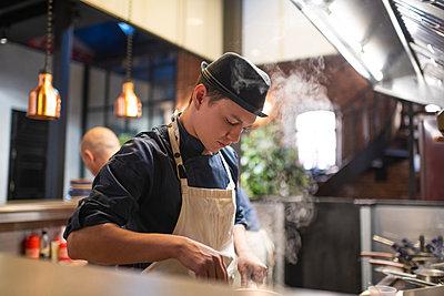 Young cook stirring food in saucepan - p1166m2250614 by Cavan Images