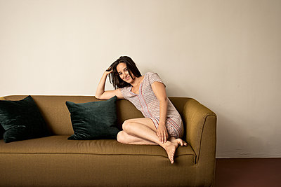 Brunette woman sits on sofa - p294m2132893 by Paolo