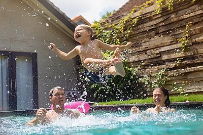 Happy family having fun in swimming pool - p300m1537386 by Konstantin Trubavin