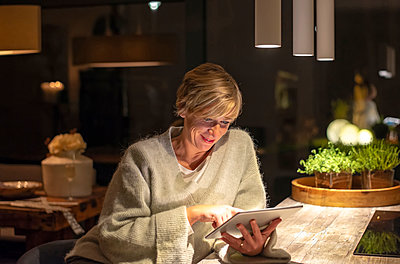Smiling blond woman working late while using digital tablet in illuminated living room - p300m2188174 by Bernd Friedel