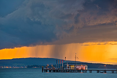 Germany, Ferry jetty and rain clouds at Lake Constance - p300m879301 by Holger Spiering