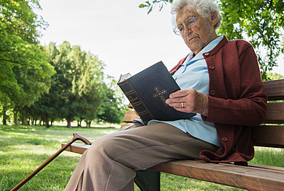 Senior woman sitting on park bench reading bible - p429m942746f by Uwe Umstaetter
