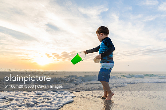 Child Swinging Bucket at the Beach While Holding a Sand Dollar - p1166m2073588 by Cavan Images
