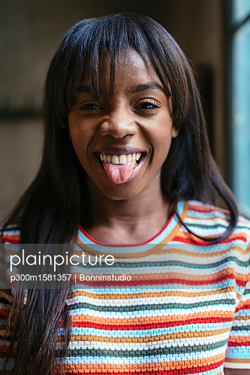 Portrait of laughing young woman sticking out tongue - p300m1581357 von Bonninstudio