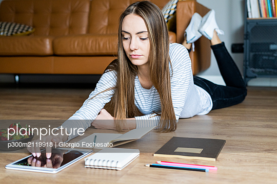 Young woman lying on the floor at home using a tablet - p300m2119918 by Giorgio Fochesato