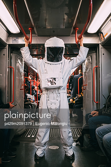 Astronaut travelling in train - p429m2091379 by Eugenio Marongiu