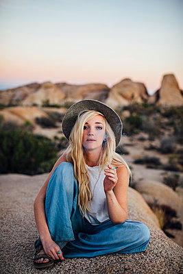 Portrait of woman smoking while sitting on rock at Joshua Tree National Park - p1166m1403066 by Cavan Images