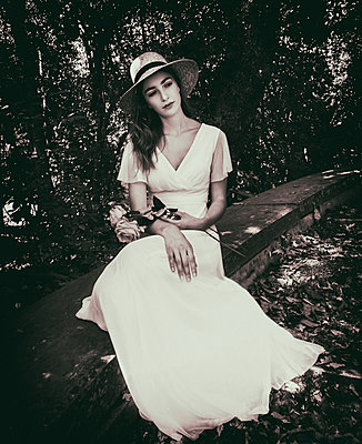 Young woman in white dress day dreaming in the garden - p1445m2184805 by Eugenia Kyriakopoulou