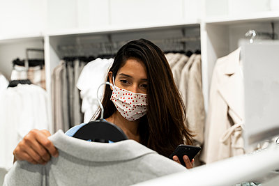 Woman wearing protective mask while looking at clothes in shopping mall - p300m2224940 by VITTA GALLERY
