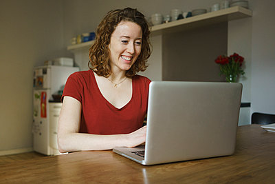 Smiling woman sitting at table using laptop in kitchen - p301m1579774 by Halfdark