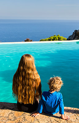 Mother and son relaxing on the edge of the pool  - p628m1476236 by Franco Cozzo