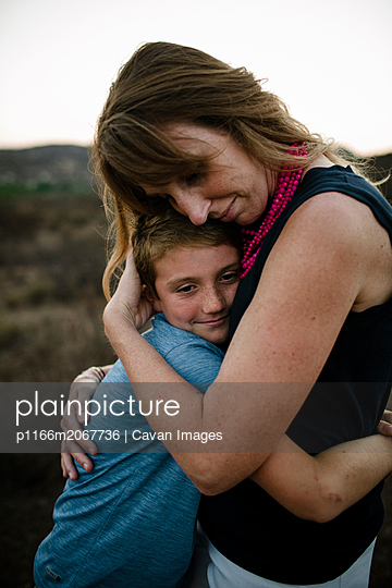 Mother and son embracing while standing on field during sunset - p1166m2067736 by Cavan Images