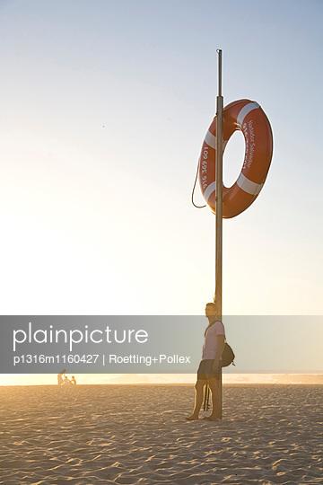 Mann am Strand bei Sonnenuntergang, rettungsring auf Pfahl, Abendlicht, Atlantik, beliebter Strand von Windsurfern, Praia de Odeceixe, Algarve, Portugal - p1316m1160427 von Roetting+Pollex