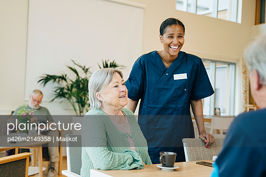 Cheerful young female nurse standing by senior woman while looking at man in retirement home - p426m2149358 by Maskot