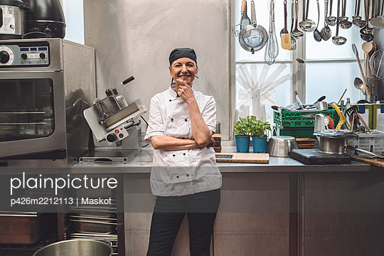 Portrait of happy mature chef with hand on chin in commercial kitchen - p426m2212113 by Maskot