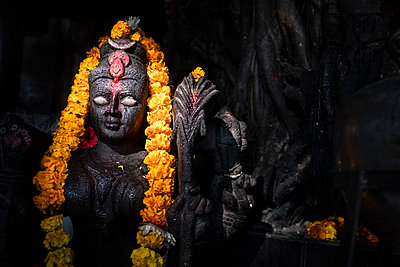 dark statue with shining eyes and flower wreath - p1007m2099041 by Tilby Vattard