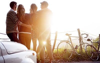 Four people standing by the side of a road, parked car and bicycles leaning against a fence, sunlight. - p1100m2214267 by Mint Images