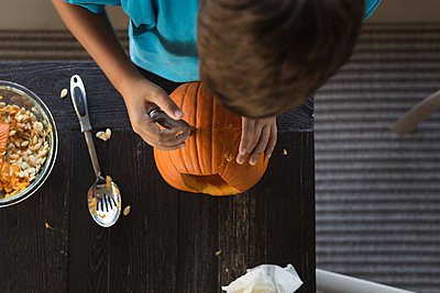 Overhead view of boy making jack o' lantern at table - p1166m1489241 by Cavan Images