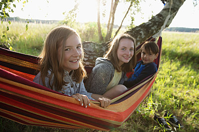 Portrait smiling brother and sisters in rural summer hammock - p1192m1490370 by Hero Images