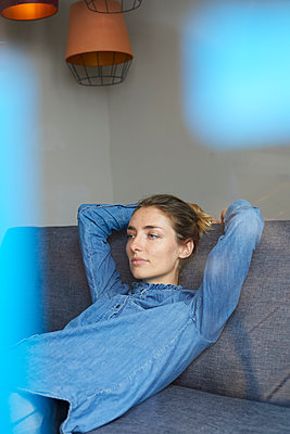 Portrait of woman wearing denim shirt relaxing on the couch - p300m1581168 von Philipp Nemenz