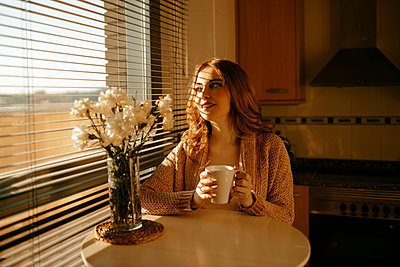 Blond woman at home drinking coffe in the kitchen in the morning - p300m2198341 by Gala Martínez López