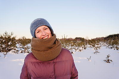 Smiling woman in warm clothing against sky during winter - p300m2265933 by Ekaterina Yakunina